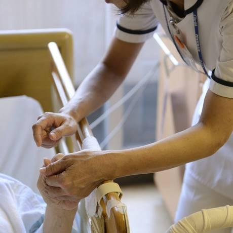 Enfermeira segura a mão de um paciente . Foto: Akio Kon / Bloomberg