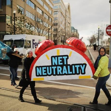 Manifestantes carregam cartazes de protesto contra o fim da neutralidade da internet nos EUA. Foto: CHIP SOMODEVILLA / AFP