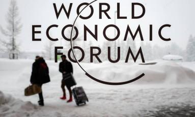 Dois participantes do Fórum Econômico Mundial, em Davos, caminham na neve para a abertura do evento. Foto: FABRICE COFFRINI / AFP