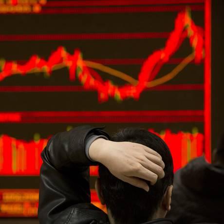 Investidor acompanha oscilação das ações em corretora de Pequim. Bolsas da Ásia fecharam em queda, acompanhando perdas de Wall Street. Foto: Mark Schiefelbein / AP