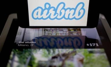 Logomarca do AirBnb ao lado de anúncios de imóveis Foto: Andrew Harrer / Bloomberg