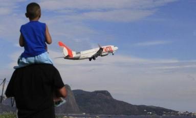 Pai e filho observam voo da Gol saindo do aeroporto Santos Dumont Foto: Agência O Globo