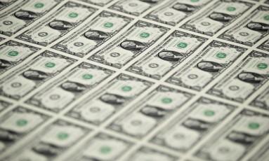 Notas de dólar antes de serem cortadas. Foto: Andrew Harrer / Bloomberg