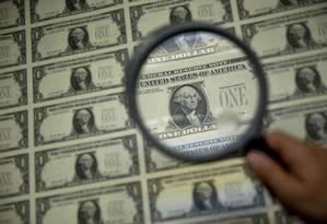 Notas de dólar são observadas através de lupa. Foto: Andrew Harrer / Bloomberg