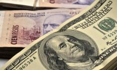 Notas de peso argentino e dólar Foto: Diego Giudice / Bloomberg News