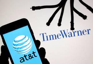 Ilustração de um smartphone com o logo da AT&T em frente a uma vitrine da Time Warner Foto: DADO RUVIC / REUTERS