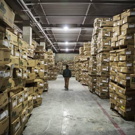 Funcionário caminha em estoque da Suzhou Huazhong Foods, com caixas de carne importada dos Estados Unidos Foto: Qilai Shen / Bloomberg