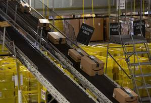 Pacotes com encomendas da Amazon passam por uma esteira na fábrica de Robbinsville, Nova Jersey. Foto: Bess Adler / Bloomberg