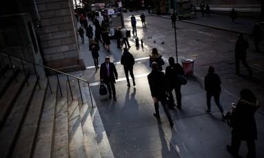 Pedestrians caminham por Wall Street, próximo da bolsa de Nova York. Foto: Michael Nagle / Bloomberg