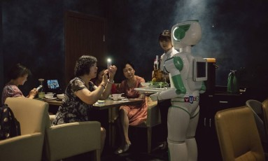 Clientes tiram foto de um robô garçom em um restaurante em Xangai. Foto: YUYANG LIU / NYT
