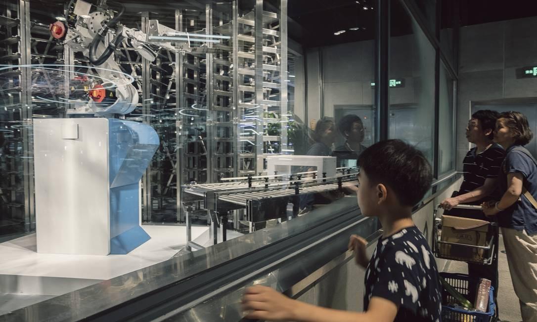 Usuários observam robôs que cozinham Foto: YUYANG LIU / NYT