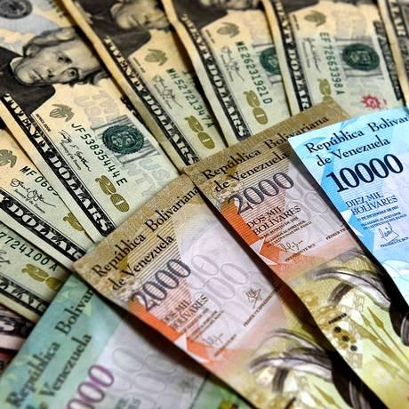 Notas de Bolívar venezuelano e de notas de dólar Foto: FEDERICO PARRA / AFP