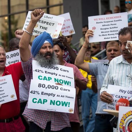 Motoristas vão às ruas de Nova York para apoiar projeto da Câmara da cidade que restringirá a concessão de licenças a motoristas de Uber e de outros aplicativos por um ano. Foto: Drew Angerer / AFP