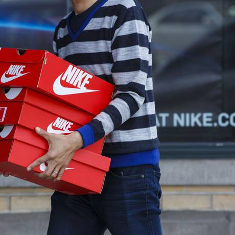 Consumidor carrega caixas da Nike em Beverly Hills, Los Angeles Foto: Patrick T. Fallon / Bloomberg