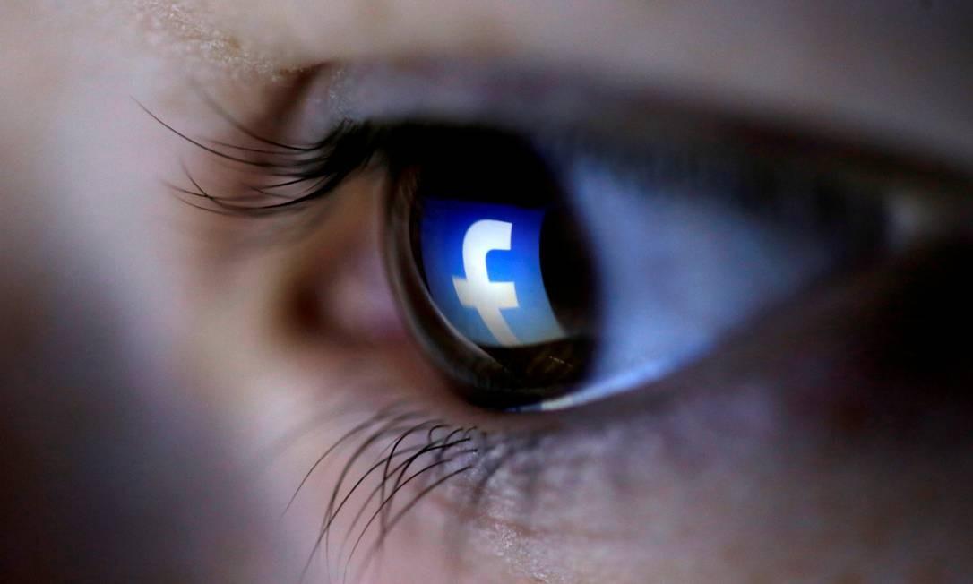 Foto mostra o logo do Facebook refletido no olho de uma pessoa. Foto: Dado Ruvic / Reuters