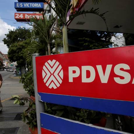 Homem caminha perto de uma placa com o logotipo da PDVSA em Caracas Foto: Marco Bello / Reuters