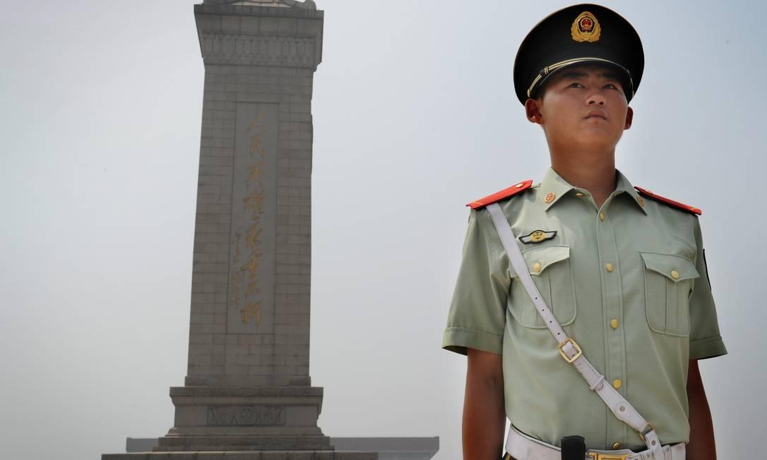 Policial chinês em frente ao Monumento aos heróis do povo, em Pequim Foto: MARK RALSTON / AFP/Getty Images