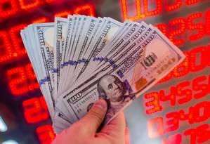 Cédulas de dólar, a moeda oficial dos Estados Unidos Foto: Yasin Akgul / AFP