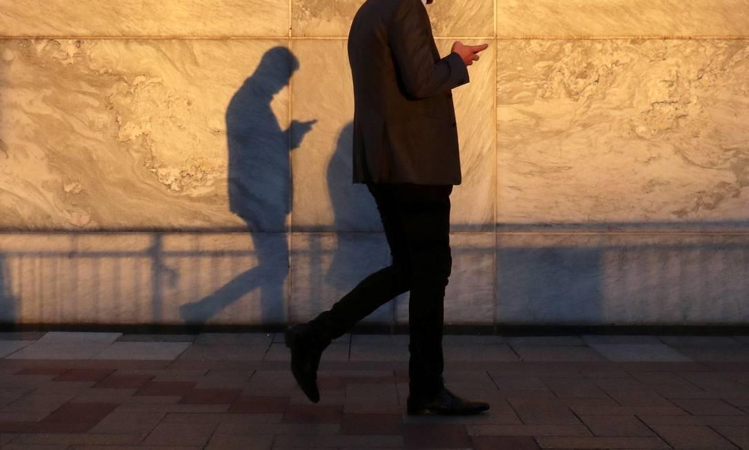 Homem caminha usando um smartphone na Canary Wharf, distrito financeiro de Londres Foto: RUSSELL BOYCE / REUTERS