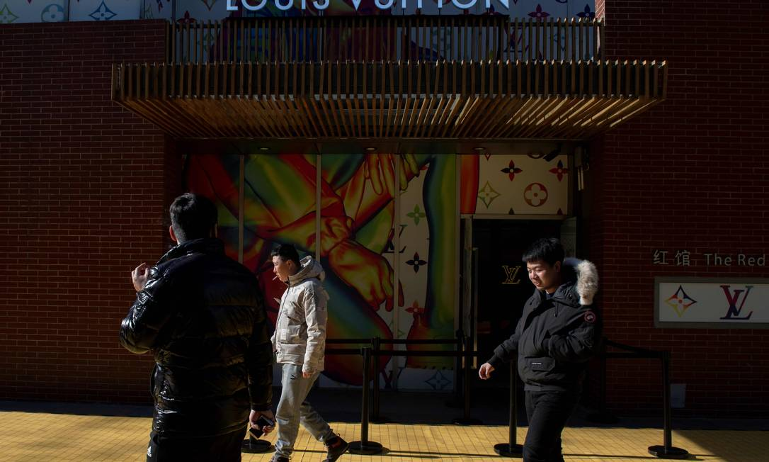 Pedestres passam em frente a uma loja da artigos de luxo em Pequim, na China Foto: Nicolas Asfouri/AFP / AFP