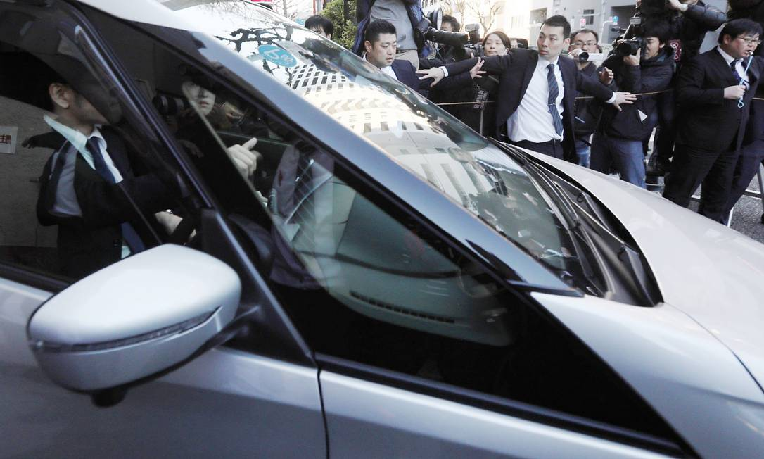 Carro, supostamente levando Carlos Ghosn de volta à prisão, deixa a casa do executivo Foto: JIJI PRESS / AFP