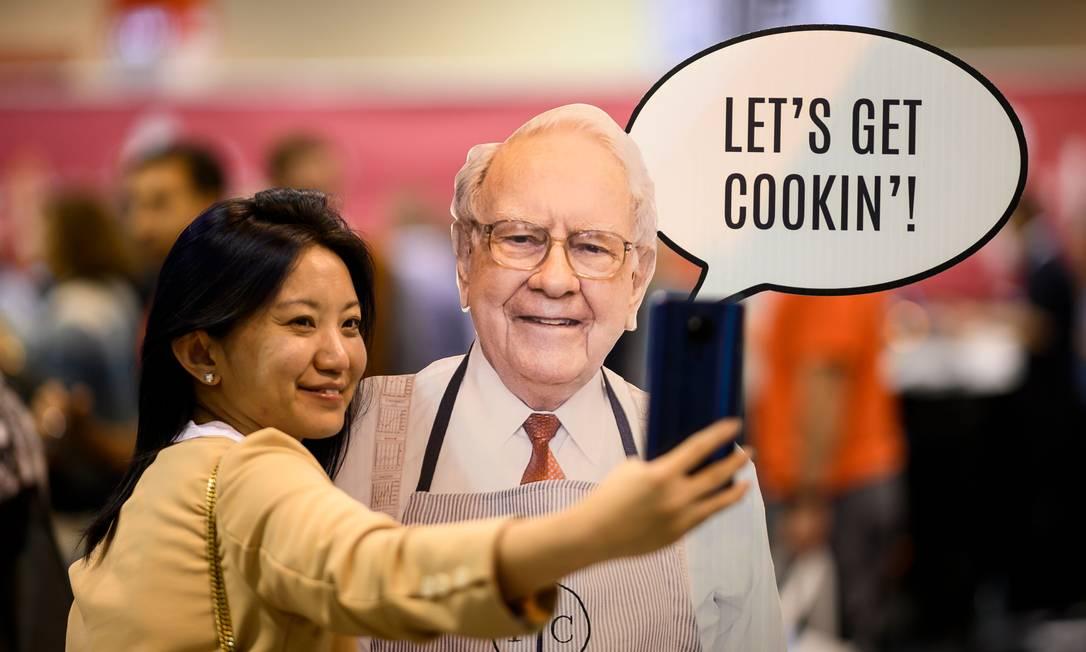 Acionista posa com imagem de Warren Buffett antes do encontro anual da Berkshire Hathaway Foto: JOHANNES EISELE / AFP