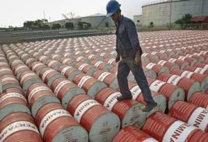 Trabalhador conta barris de petróleo Foto: Agência O Globo