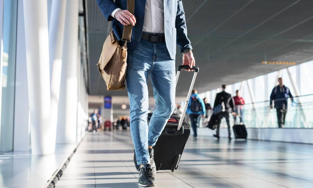 Passageiro carrega mala em saguão de aeroporto Foto: Kaspars Grinvalds / Kaspars Grinvalds - stock.adobe.