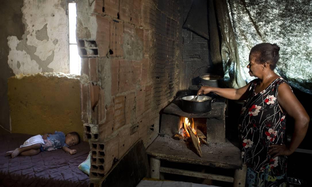 Números da Pesquisa Nacional por Amostra de Domicílios Contínua (Pnad) mostram aumentou do número de famílias que usam a lenha ou carvão para cozinhar. Juranir Nobre Mange, que mora na comunidade Vale dos Eucalíptos, cozinha no fogão a lenha enquanto um dos seis netos dorme no quarto. Falta dinheiro para comprar botijão de gás Foto: Márcia Foletto / Agência O Globo