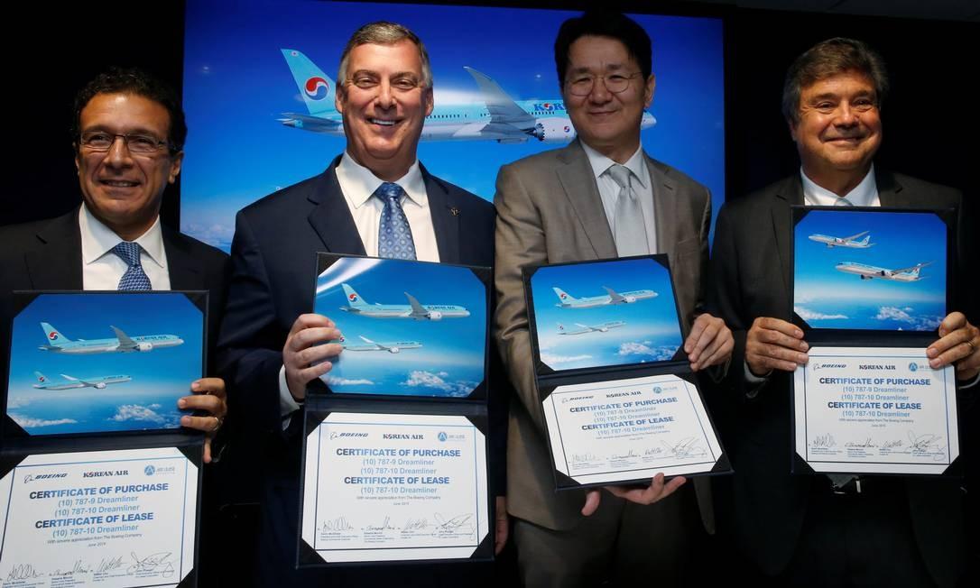 Vice-presidente de aviões comerciais da Boeing, Ihassane Mounir, o CEO Kevin McAllister, o CEO da Korean Air, Walter Cho e o Ceo da Air Lease, John Plueger, posam com o certificado de compra do Boeing 787 Dreamliner Foto: Pascal Rossignol / REUTERS