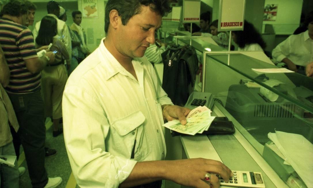 Após a entrada em vigor da nova moeda, os brasileiros foram aos bancos para trocar as notas de cruzado real pelo real. Na imagem, cliente de um banco no Rio fazendo a troca em 1º de julho de 1994 Foto: Agência O Globo