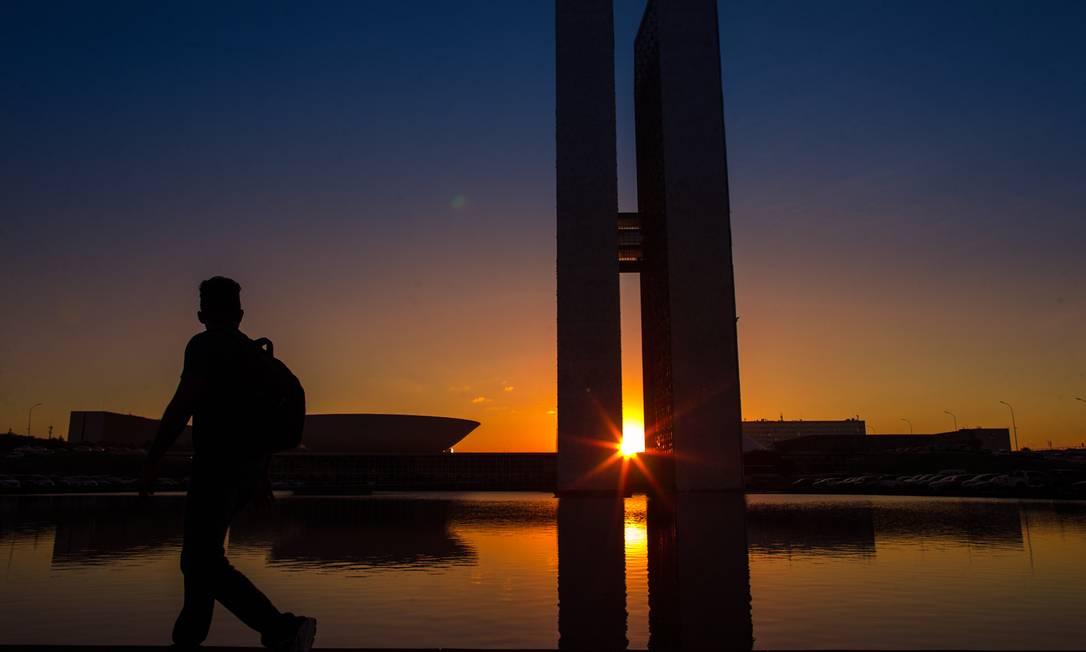 Homem passa por trás do Congresso Nacional em um final de tarde Foto: Daniel Marenco / Agência O Globo
