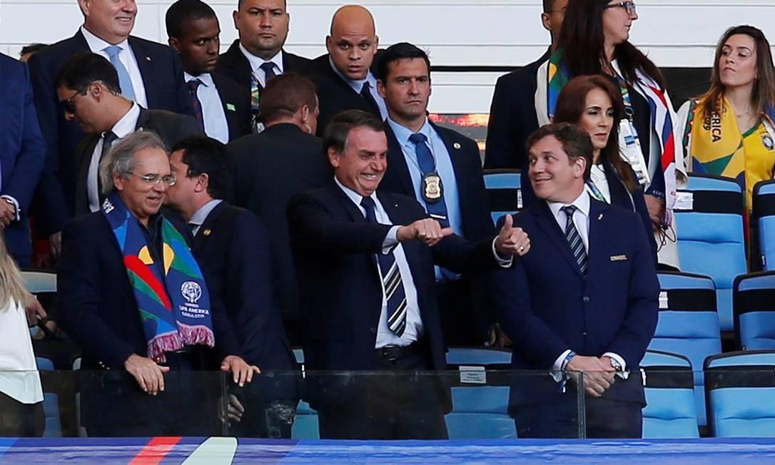 Ministro da Economia, Paulo Guedes, ao lado do presidente Jair Bolsonaro, em tribuna no Maracanã, no jogo entre Brasil e Peru pela final da Copa América. Foto: Luisa Gonzales / Reuters