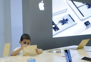 Criança usa um aparelho em uma Apple Store, em Moscou Foto: Reuters