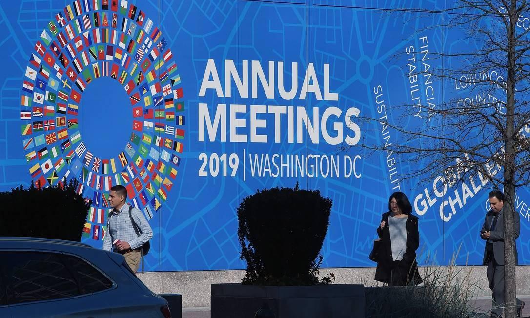 Pessoas passam em frente ao prédio onde acontecem as reuniões de outono do FMI e do Banco Mundial, em Washington, DC Foto: OLIVIER DOULIERY / AFP