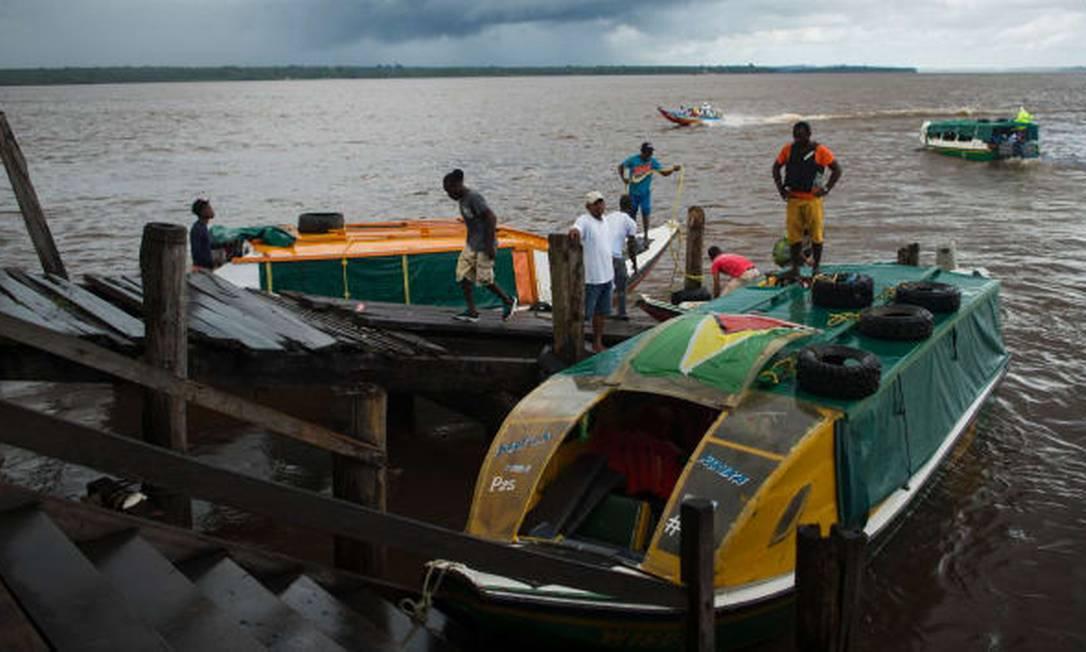 Táxis fluviais aguardam passageiros no deque da cidade de Bartica, na Guiana Foto: AFP