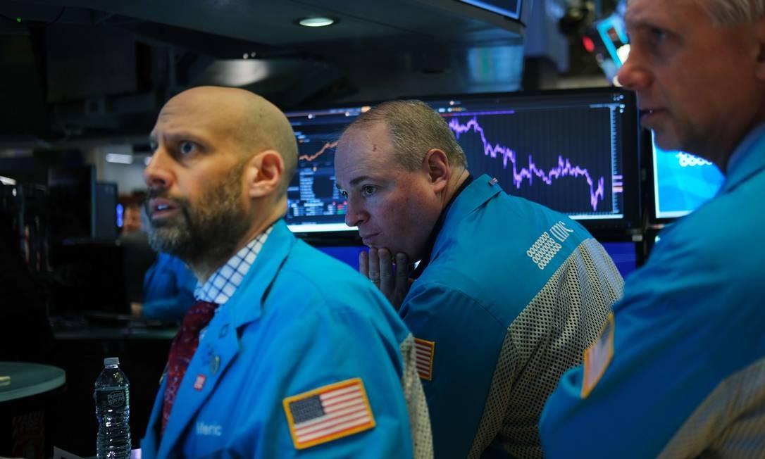 Operdores da Bolsa de Nova York atentos às oscilações das ações, já que os temores sobre a disseminação do coronavírus continuam perturbando os mercados globais. Foto: Spender Platt / AFP