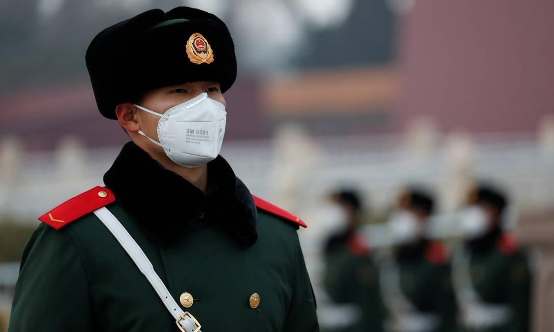 Um oficial usando máscara facial guarda o portão de Tiananmen, em Pequim, enquanto o país é atingido por um surto do novo coronavírus Foto: Carlos Garcia Rawlins / Reuters