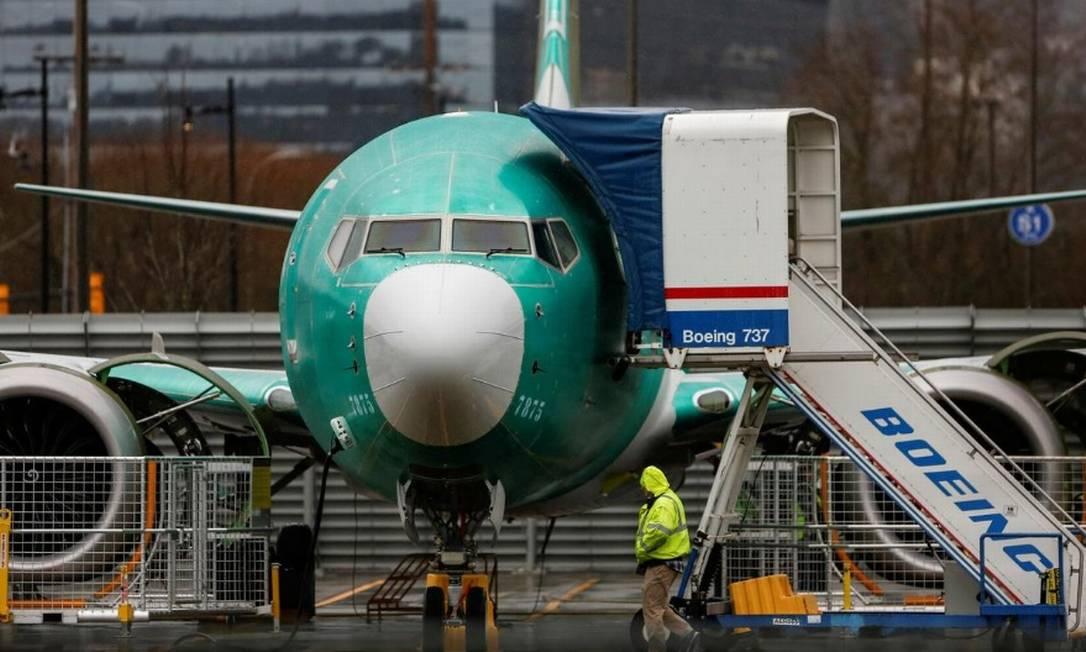Funcionário passa por um jato 737 Max estacionado no aeroporto municipal de Renton , Washington Foto: Reuters