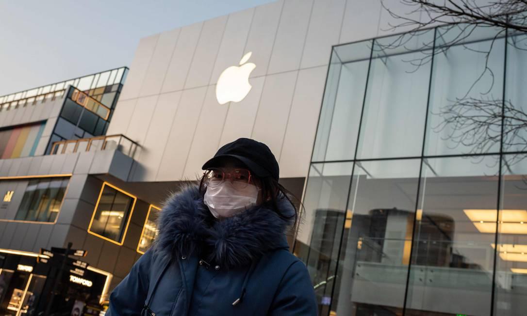Uma mulher usando uma máscara protetora caminha em frente a uma loja da Apple fechada em Pequim Foto: Nicolas Asfouri / AFP