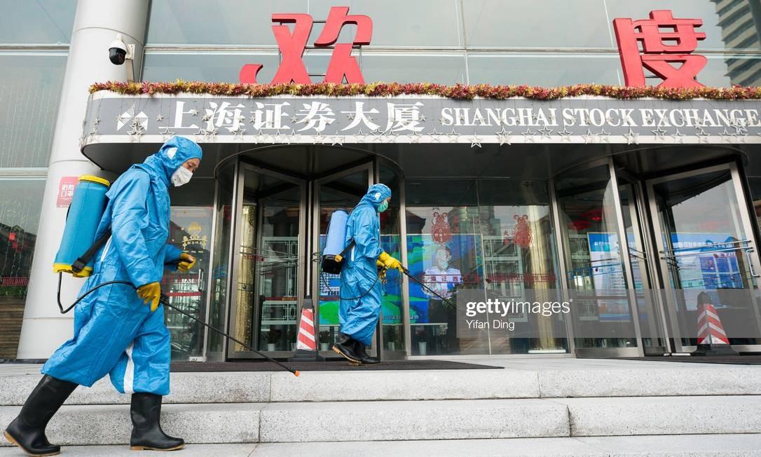 Equipes médicas jogam spray antisséptico na principal entrada da Bolsa de Xangai Foto: Yifan Ding / Getty Images