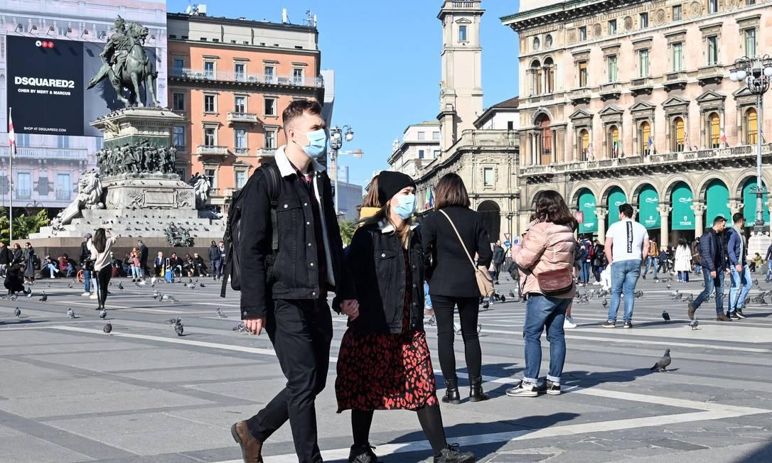 Casal caminha pela Praça da Catedral (Milão) vestindo máscaras cirúrgicas em meio ao surto de coronavírus na região Foto: Andreas Solaro / AFP