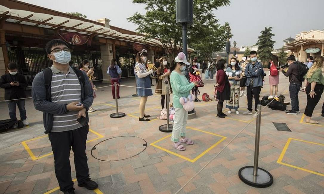 Visitantes de máscara fazem distanciamento em fila de parque da Disney na China Foto: Qilai Shen/Bloomberg