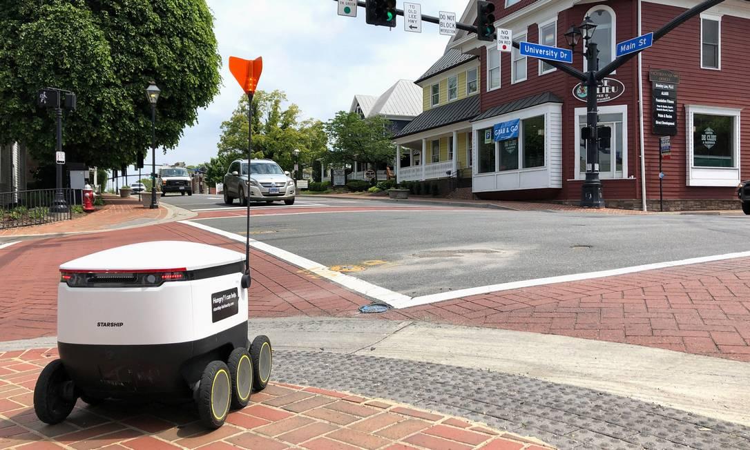Robô de entregas da Starship aguarda o sinal de pedestres abrir para atravessar uma rua de Fairfax, na Virginia Foto: Julio Cesar Chavez / Reuters
