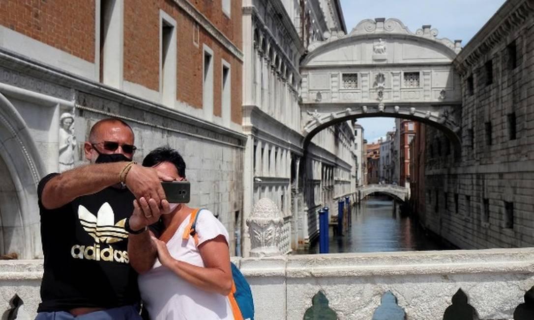 Turistas com máscaras de proteção posam para foto em frente à Ponte dos Suspiros, em Veneza Foto: Reuters