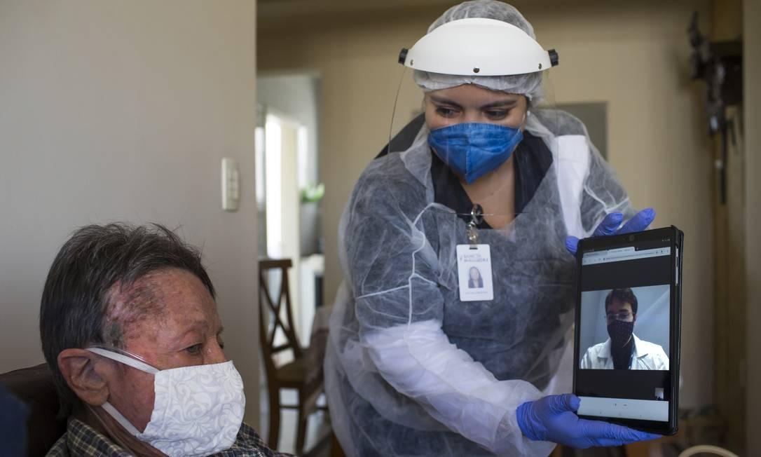 Cuidado redobrado - A enfermeira Natyela auxilia Irede (a esquerda) e sua irmã, Juçara, durante uma consulta on-line Foto: Edilson Dantas / Agência O Globo