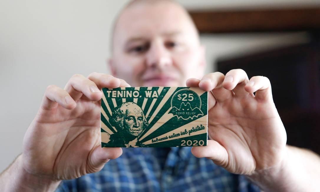 """Prefeito de Tenino Wayne Fournier segurando uma nota de 25 """"dólares Covid"""" Foto: Jason Redmond / AFP"""