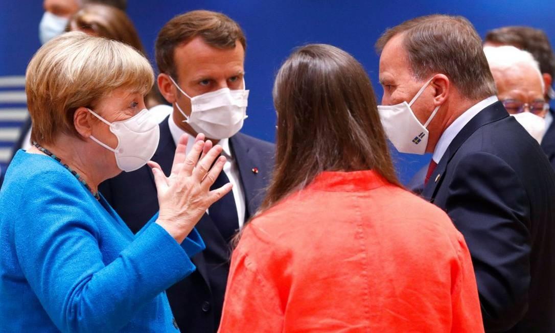 A chanceler da Alemanha, Angela Merkel, gesticua ao falar com o presidente francês, Emmanuel Macron, e com o primeiro-ministro sueco, Stefan Lofven, na cúpula em Bruxelas Foto: FRANCOIS LENOIR / AFP