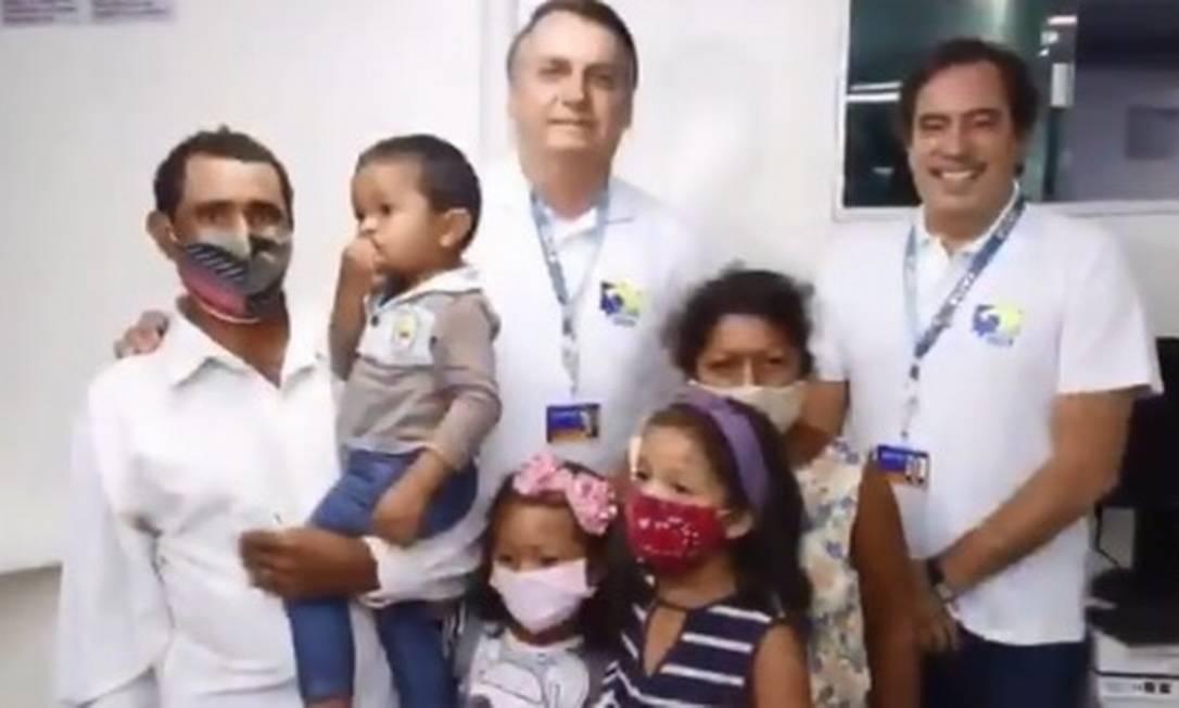 Sem máscaras, Bolsonaro e o presidente da Caixa, Pedro Guimarães, posam com uma família durante atendimento em agência-barco em Breves (PA), na Ilha do Marajó Foto: Reprodução/Redes sociais