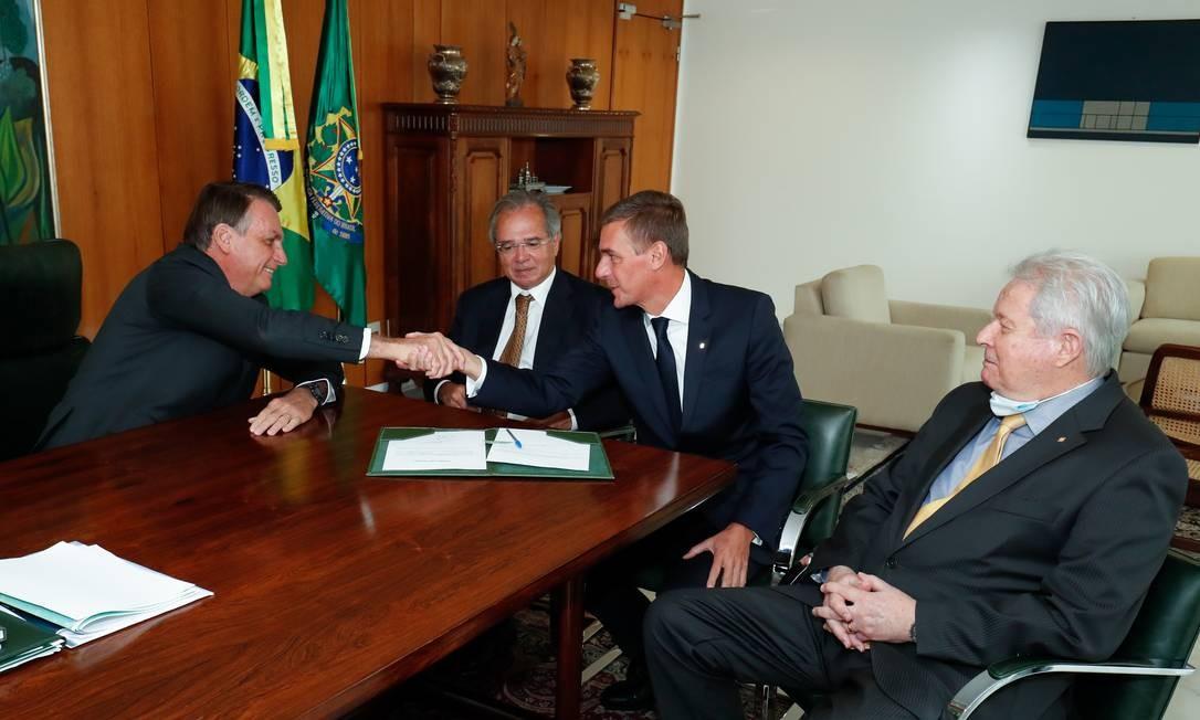 Alternativa: Bolsonaro cumprimenta André Brandão na posse, ao lado do ministro Paulo Guedes: opção ao fechamento de agências é reduzir aluguel de imóveis Foto: Agência O Globo
